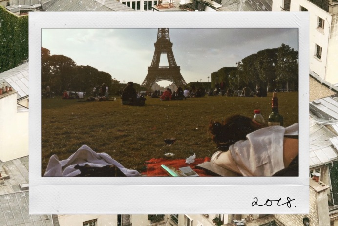 A polaroid of the Eiffel Tower from Champs de Mars, with Parisian rooftops in the background - WILDCHILD
